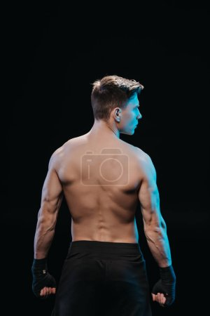 Photo for Back view of muscular sportsman in bandages and blue light isolated on black - Royalty Free Image