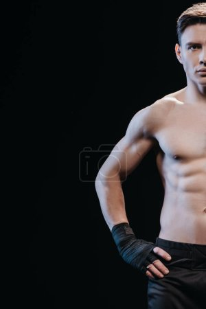 Photo for Partial view of muscular sportive boxer in bandages isolated on black - Royalty Free Image