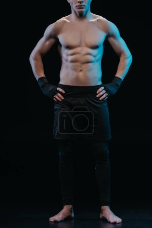 Photo for Partial view of muscular barefoot boxer in bandages standing with hands on hips - Royalty Free Image