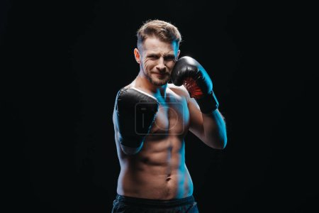 Photo for Muscular shirtless strenuous boxer in boxing gloves doing punch at camera isolated on black - Royalty Free Image