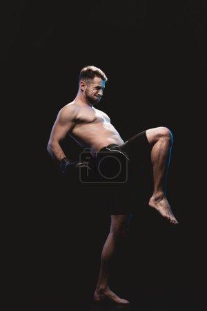 Photo pour Musculaire boxer intense pieds nus dans les gants de boxe faisant coup isolé sur fond noir - image libre de droit
