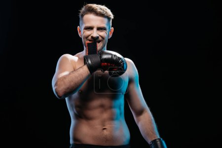 muscular sporty boxer taking off  boxing gloves with mouth isolated on black