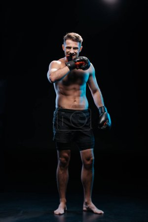 Photo for Muscular barefoot sporty boxer taking off  boxing gloves with mouth on black - Royalty Free Image