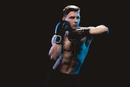 Photo for Confident muscular sporty boxer in boxing gloves doing punch isolated on black - Royalty Free Image