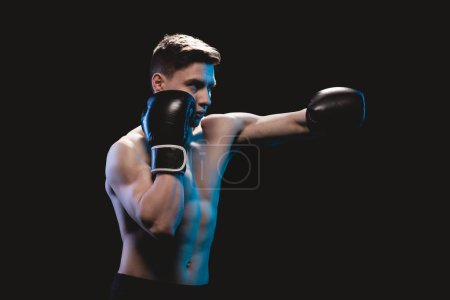 Photo for Muscular mma fighter in boxing gloves doing punch isolated on black - Royalty Free Image