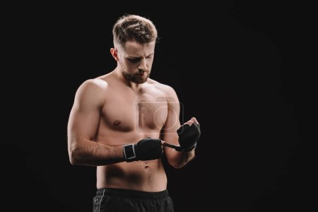 Photo for Strong muscular mma fighter fixing bandages isolated on black - Royalty Free Image