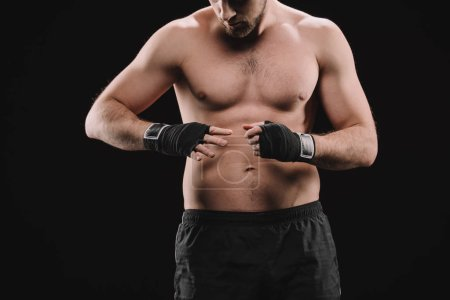 Photo for Partial view of muscular sportsman looking at hands with bandages isolated on black - Royalty Free Image
