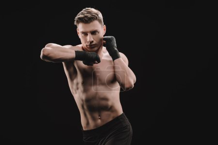 Photo for Athletic muscular sportsman in bandages doing punch with elbow isolated on black - Royalty Free Image
