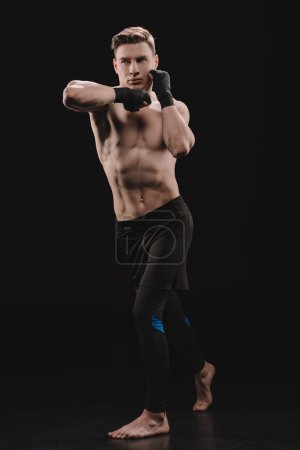 Photo for Full length of athletic muscular sportsman in bandages doing punch with elbow on black - Royalty Free Image