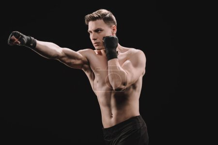 Photo for Strong shirtless muscular sportsman in bandages doing punch isolated on black - Royalty Free Image