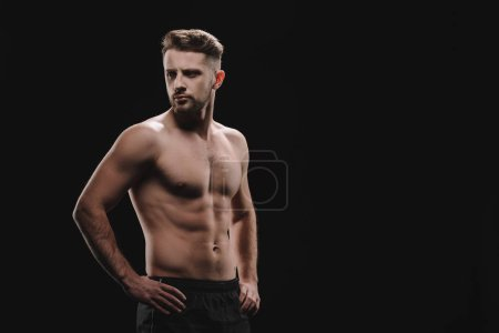 Photo for Strong athletic muscular sportsman with hands on hips looking away isolated on black - Royalty Free Image