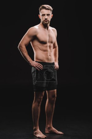 Photo for Athletic barefoot muscular sportsman with hands on hips on black - Royalty Free Image
