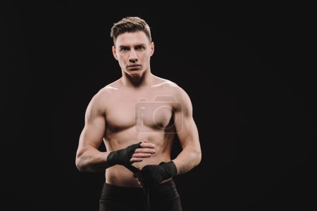 Photo for Strong shirtless muscular mma fighter fixing bandages and looking at camera isolated on black - Royalty Free Image