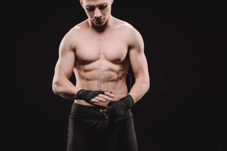 Photo for Strong shirtless muscular mma fighter fixing bandages isolated on black - Royalty Free Image