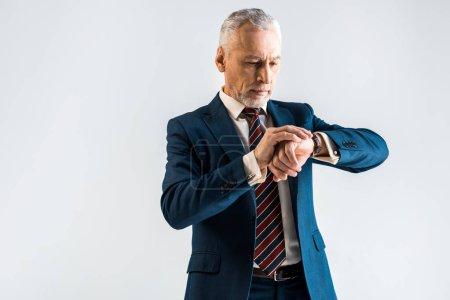 Foto de Empresario maduro guapo en traje de pie y mirando el reloj aislado en gris - Imagen libre de derechos