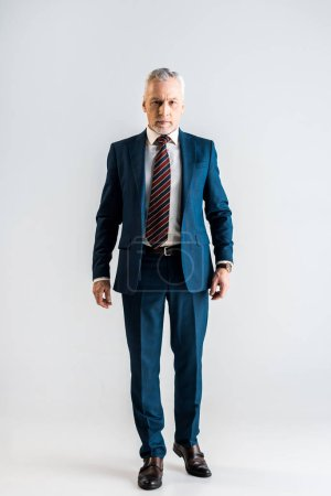 Photo for Serious middle aged businessman in suit standing on grey - Royalty Free Image