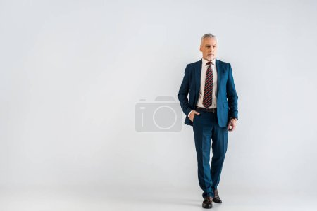 pensive mature businessman in suit standing with hand in pocket on grey