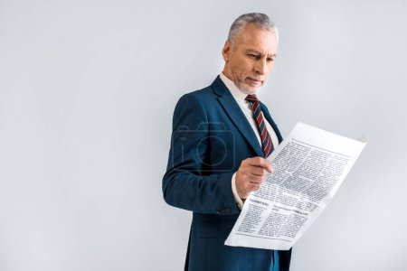 Photo for Mature businessman reading newspaper while standing isolated on grey - Royalty Free Image