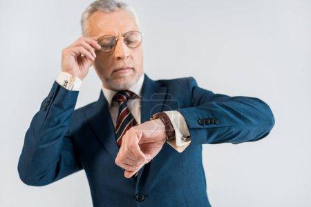Photo pour Mise au point sélective de mature homme d'affaires touchant des lunettes et regardant montre isolé sur fond gris - image libre de droit
