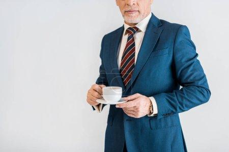 Foto de Vista recortada del empresario maduro en ropa formal con platillo y taza aislada en gris - Imagen libre de derechos
