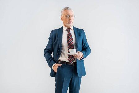 Photo pour Sérieux homme d'affaires mature tenant soucoupe avec tasse et debout avec la main dans la poche isolé sur gris - image libre de droit