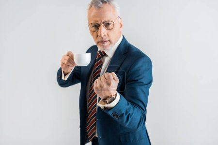 Photo for Confident mature businessman holding cup and showing fist isolated on grey - Royalty Free Image