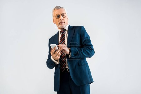 mature businessman in suit holding smartphone isolated on grey