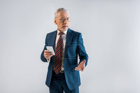 mature businessman in suit holding smartphone and gesturing isolated on grey