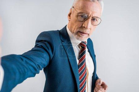 Photo pour Mature homme d'affaires en costume tenant selfie et regardant la caméra isolée sur fond gris - image libre de droit