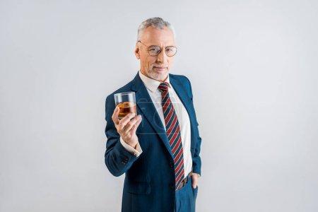 Photo pour Gai homme mature tenant le verre de whisky en se tenant debout avec les mains en poche isolée sur fond gris - image libre de droit