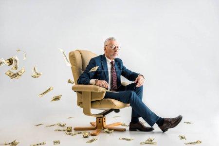 Photo pour Foyer sélectif d'homme d'affaires mature confiant assis dans un fauteuil près de billets en dollars sur gris - image libre de droit