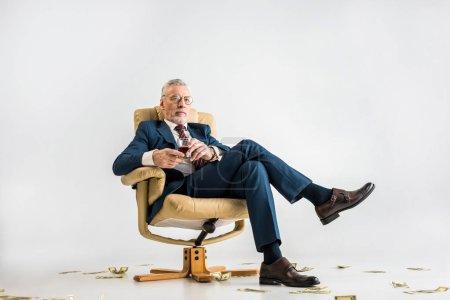 Photo pour Homme d'affaires mature en costume assis dans un fauteuil près de billets en dollars et tenant un verre de whisky sur gris - image libre de droit
