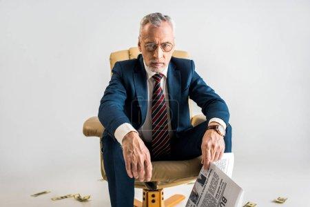 Photo pour Homme d'affaires mature assis dans le fauteuil près de billets en dollar et en tenant le journal d'affaires isolé sur fond gris - image libre de droit