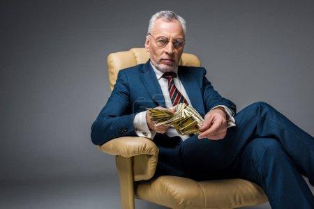 Photo pour Homme d'affaires mature sérieuse assis dans le fauteuil et détenant des billets de dollar sur fond gris - image libre de droit