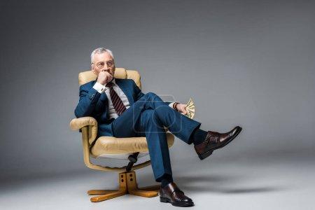 Photo pour Homme d'affaires mature réfléchi assis dans un fauteuil et tenant des billets en dollars sur gris - image libre de droit