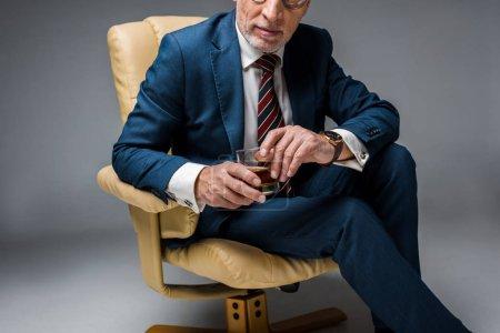 vue recadrée d'un homme d'affaires mature assis dans un fauteuil et tenant un verre de whisky sur du gris