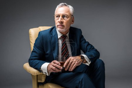 środku wieku biznesmen w garnitur, siedząc w fotelu i trzymając szklankę whisky na szary