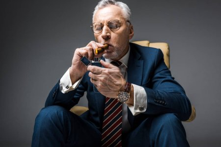 Photo for Mature businessman holding lighter while smoking cigar with closed eyes on grey - Royalty Free Image