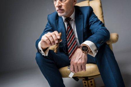 Photo pour Homme mature en costume tenant cigare et plus léger tout en étant assis dans un fauteuil sur gris - image libre de droit