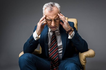 tired mature businessman in suit having headache while sitting in armchair on grey