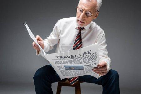 Photo pour Homme d'affaires mature dans des verres de lecture de journal de voyage sur fond gris - image libre de droit