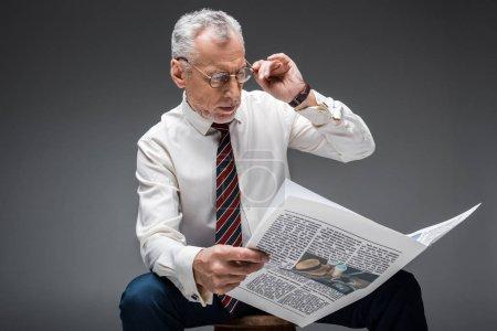 Photo pour Mature homme d'affaires touchant des lunettes tout en lisant le journal sur fond gris - image libre de droit