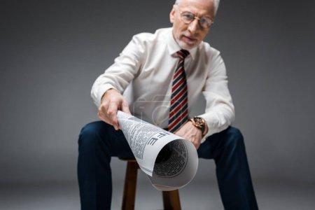 foco selectivo del periódico en la mano del hombre de negocios maduro en gris
