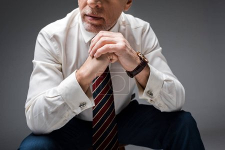 Photo for Cropped view of mature businessman with clenched hands on grey - Royalty Free Image