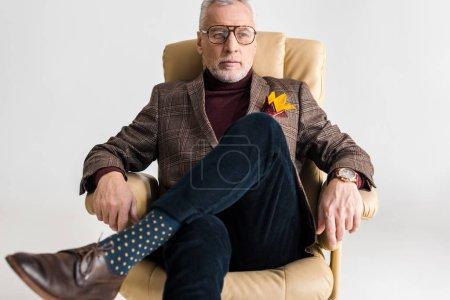 Photo pour Homme âgé moyen dans des verres, assis dans le fauteuil avec les jambes croisées isolés sur fond gris - image libre de droit