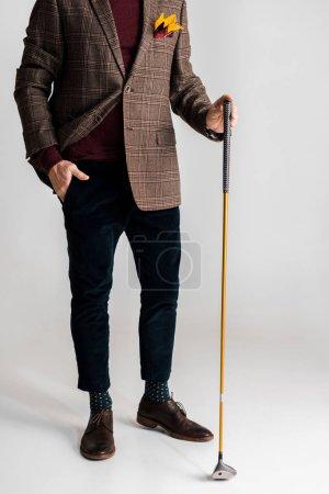 Photo for Cropped view of stylish mature man holding golf club and while standing with hand in pocket on grey - Royalty Free Image
