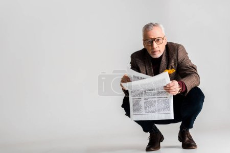 Photo for Trendy mature man in glasses holding newspaper while sitting on grey - Royalty Free Image
