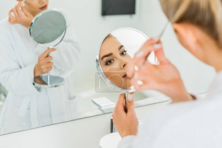 Photo for Selective focus of beautiful woman plucking eyebrows with tweezers in bathroom - Royalty Free Image