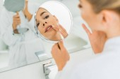 selective focus of woman touching face and looking at mirror in bathroom
