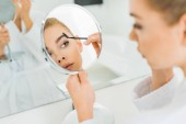 selective focus of attractive woman brushing eyebrows and looking at mirror in bathroom